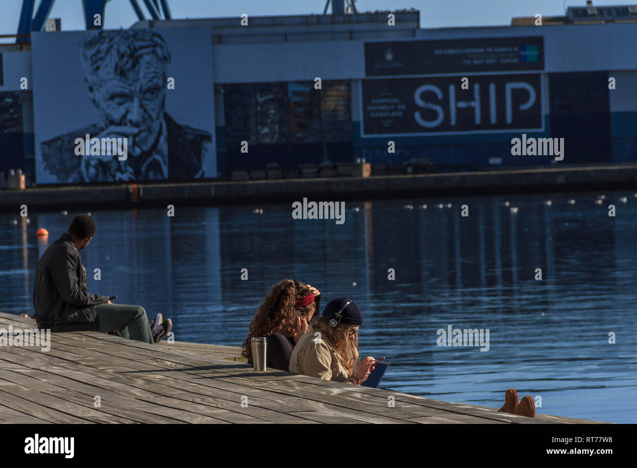 Students relaxing in the sun by the harbour during a period of unseasonably warm weather at Aarhus, Denmark. Temperatures reached 16C although the February average is 6C. Aarhus, Denmark. February 2019. - Stock Image