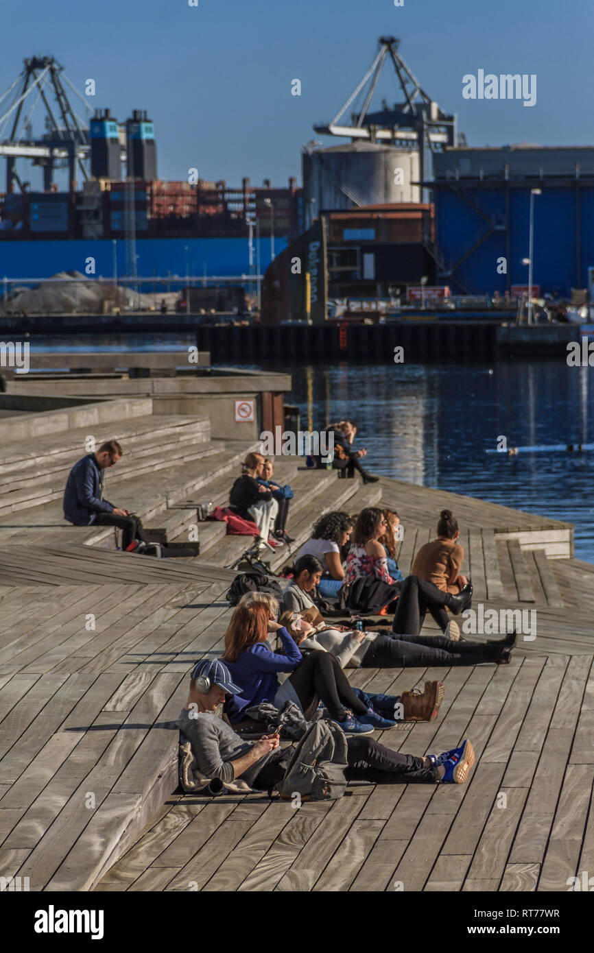 Aarhus, Denmark 28th February, 2019. Students relax in the sun by the harbour during a period of unseasonably warm weather at Aarhus, Denmark. Temperatures have reached 16C over the last week, though the February average is 6C. - Stock Image