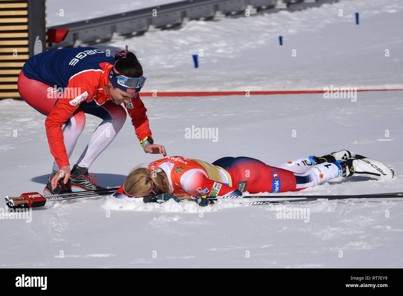 Seefeld, Austria, 28th February, 2019. How hot was it? So hot that the Norwegian Ski Team's number 1 skier, Therese Johaug, took an immediate dive into the snow after finishing the anchor leg of the women's relay at the nordic world ski championships.  Temperatures were in the 50s. Norway finished fifth.  Temate Heidi Weng approaches Johaug. © John Lazenby/Alamy Live News. - Stock Image