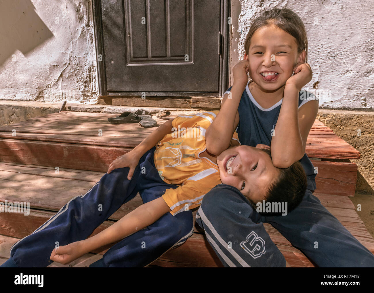 Kazakh brother and sister hamming it up for the camera, Altyn Emel Naitonal Park, Kazakhstan - Stock Image