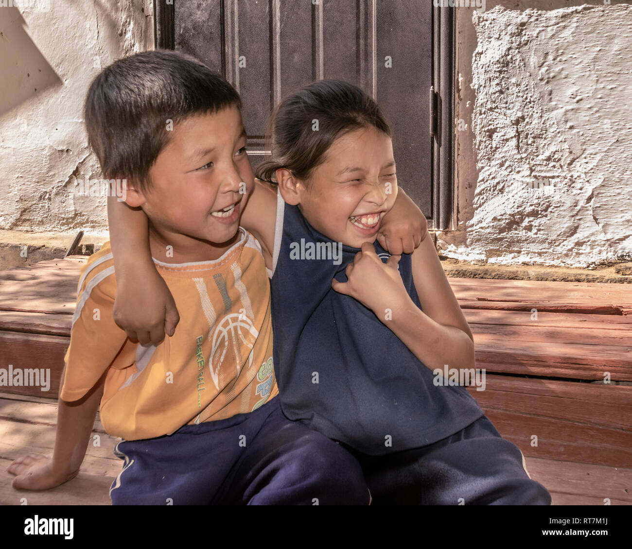 Kazakh brother and sister hamming it up on their front step, Altyn Emel Naitonal Park, Kazakhstan - Stock Image
