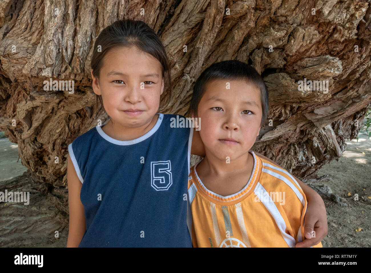 Kazakh brother and sister by a 700 year old willow tree, Altyn Emel National Park, Kazakhstan - Stock Image