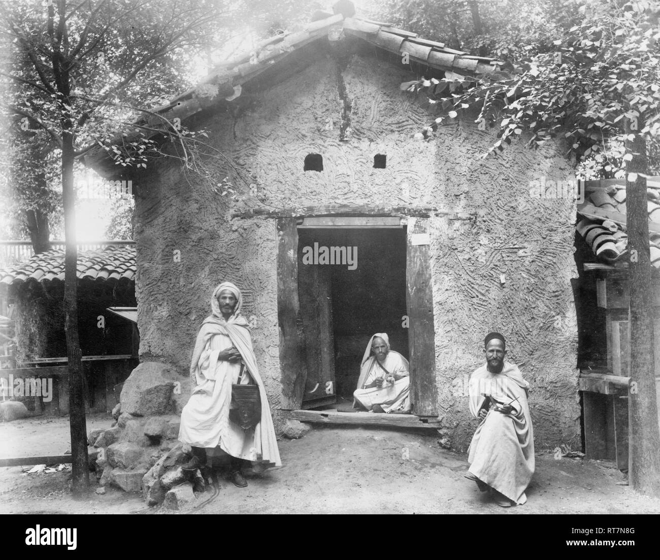 Three Arab men sitting in front of Kabyle house, Paris Exposition, 1889 - Stock Image
