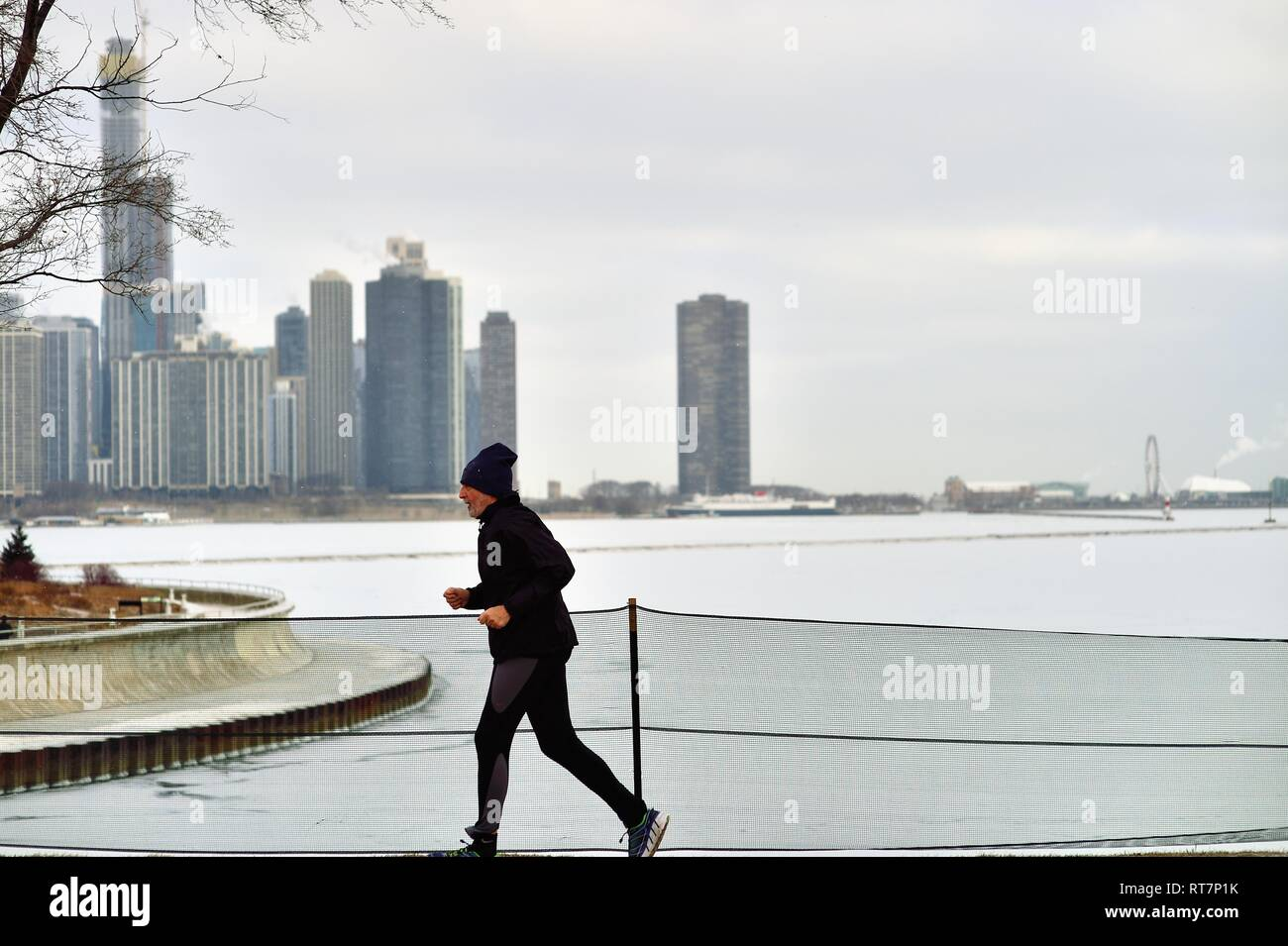 Chicago, Illinois, USA. A lone runner jogs along the Chicago Museum Campus in front of an ice-laden Lake Michigan and a portion of the city skyline. - Stock Image