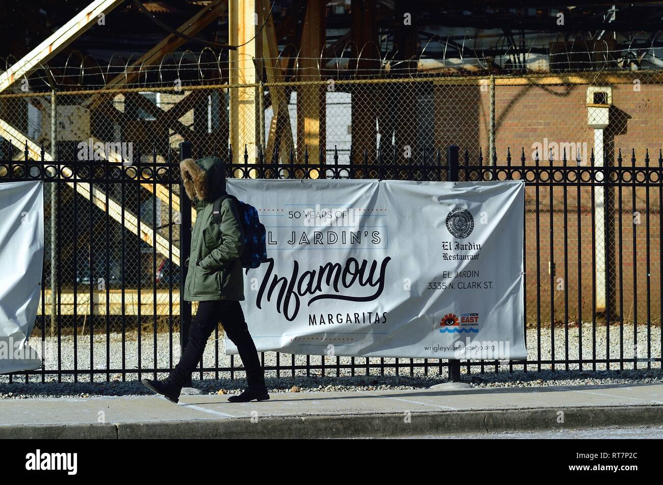 Chicago, Illinois, USA. Man walking along Clark Street dressed for a cold winer morning on Chicago's North Side in the Wrigleyville area. - Stock Image