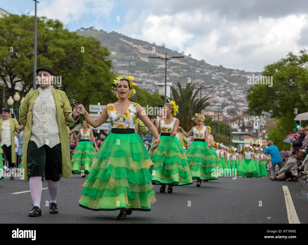Funchal; Madeira; Portugal - April 22; 2018: a group of people  in colorful dresses with sunflowers motifs are dancing at Madeira Flower Festival Para - Stock Image