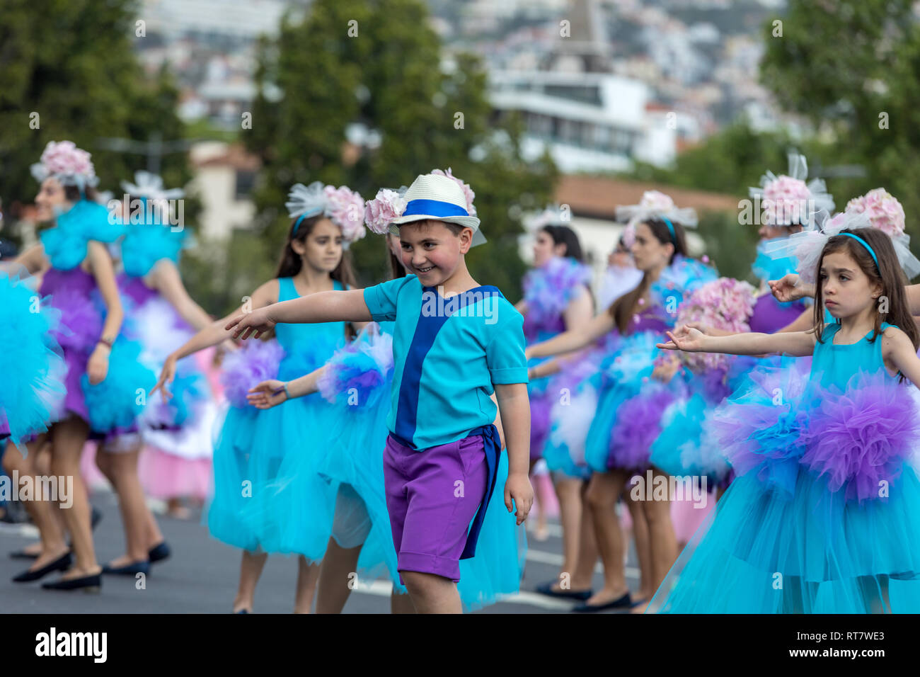 Funchal; Madeira; Portugal - April 22; 2018: A group of children in colorful costumes are dancing at Madeira Flower Festival Parade in Funchal on the  - Stock Image