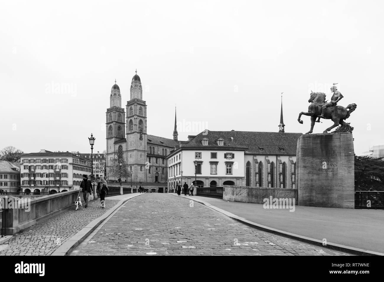 Switzerland, Zurich. Black and white picture of the Grossmuenster church and the Muenster bridge in the old town during a foggy autumn day. Picture ta - Stock Image