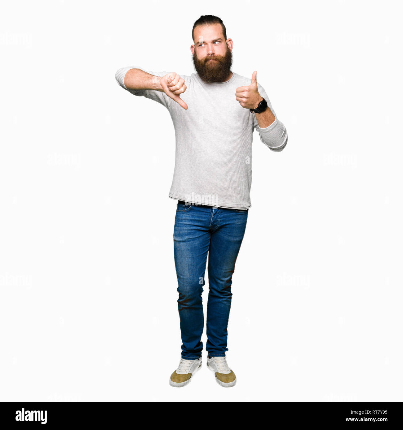 Young blond man wearing casual sweater Doing thumbs up and down, disagreement and agreement expression. Crazy conflict - Stock Image