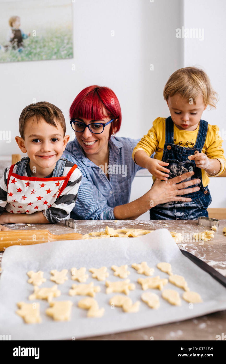 Mother baking cookies with her children - Stock Image