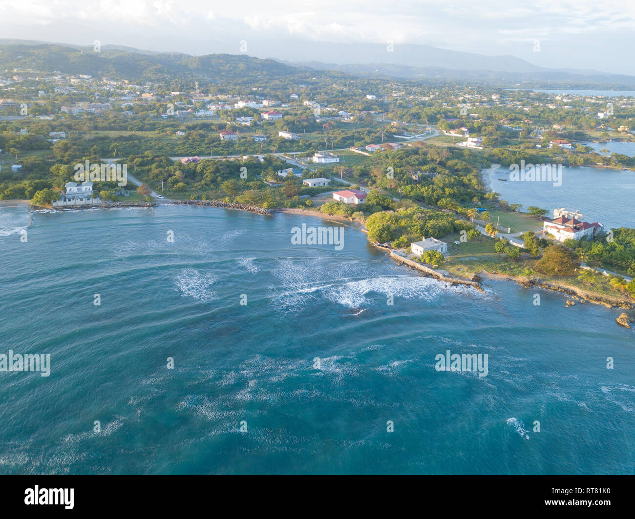 Aerial Drone shot of Jamaica, showing the Caribbean sea, houses and mountain - Stock Image