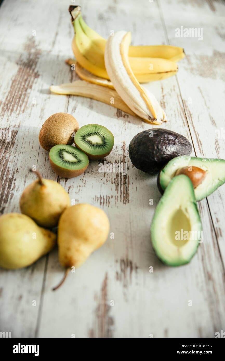Pears, peeled and whole banana, sliced and whole avocado and kiwi - Stock Image