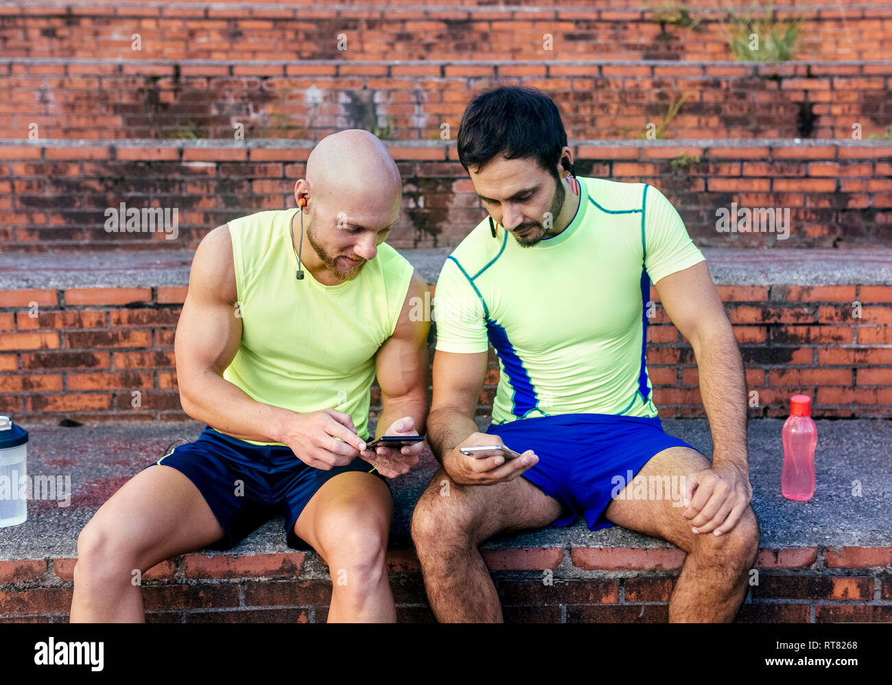 Two athletes sharing smartphones after workout - Stock Image