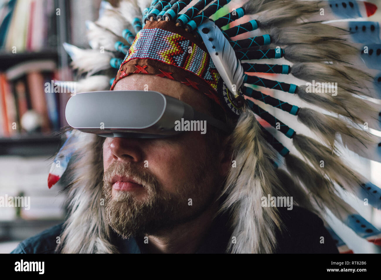Man wearing Indian headdress and VR glasses in office - Stock Image