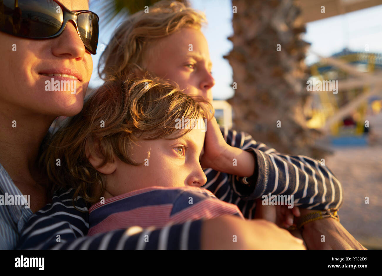 Mother with two sons on the beach at sunset Stock Photo