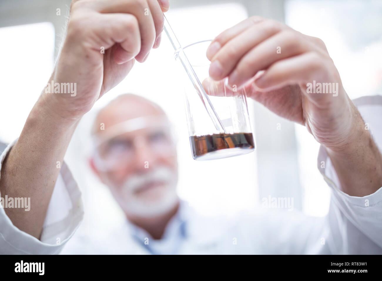 Man holding beaker in laboratory - Stock Image