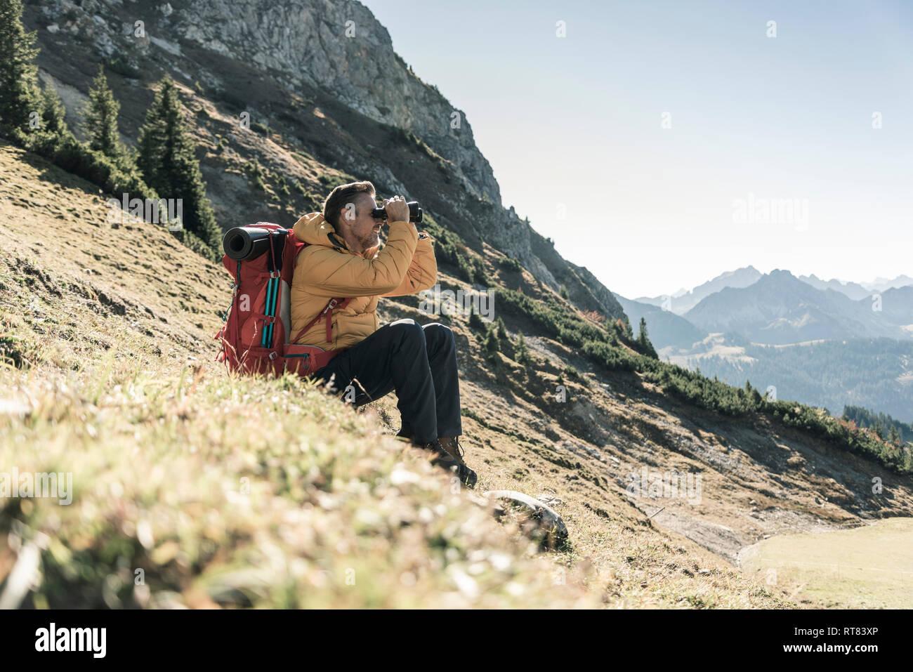 Austria, Tyrol, man having a break during a hiking trip in the mountains looking through binoculars Stock Photo