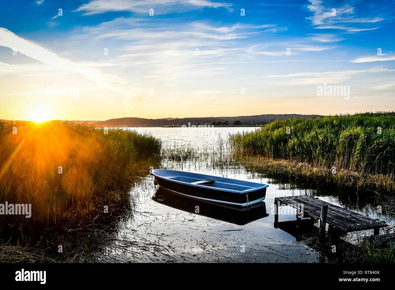 Germany, Mecklenburg-Western Pomerania, Ruegen, Sellin, empty rowing boat near jetty at sunset Stock Photo