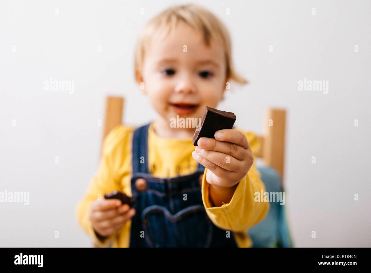 Hand of smiling toddler girl holding piece of chocolate, close-up - Stock Image