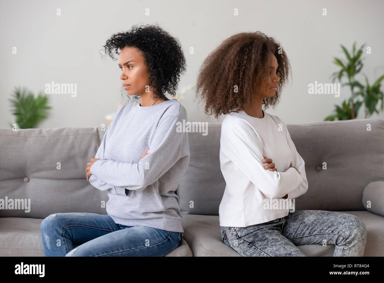 African family daughter mother sitting on couch separately after quarrel - Stock Image
