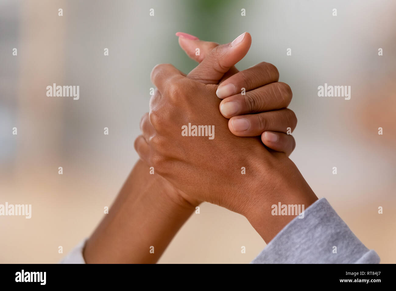 Close up of african females arm wrestling - Stock Image