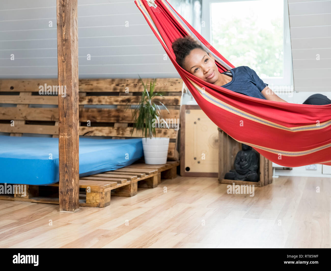 Smiling young woman lying in hammock - Stock Image