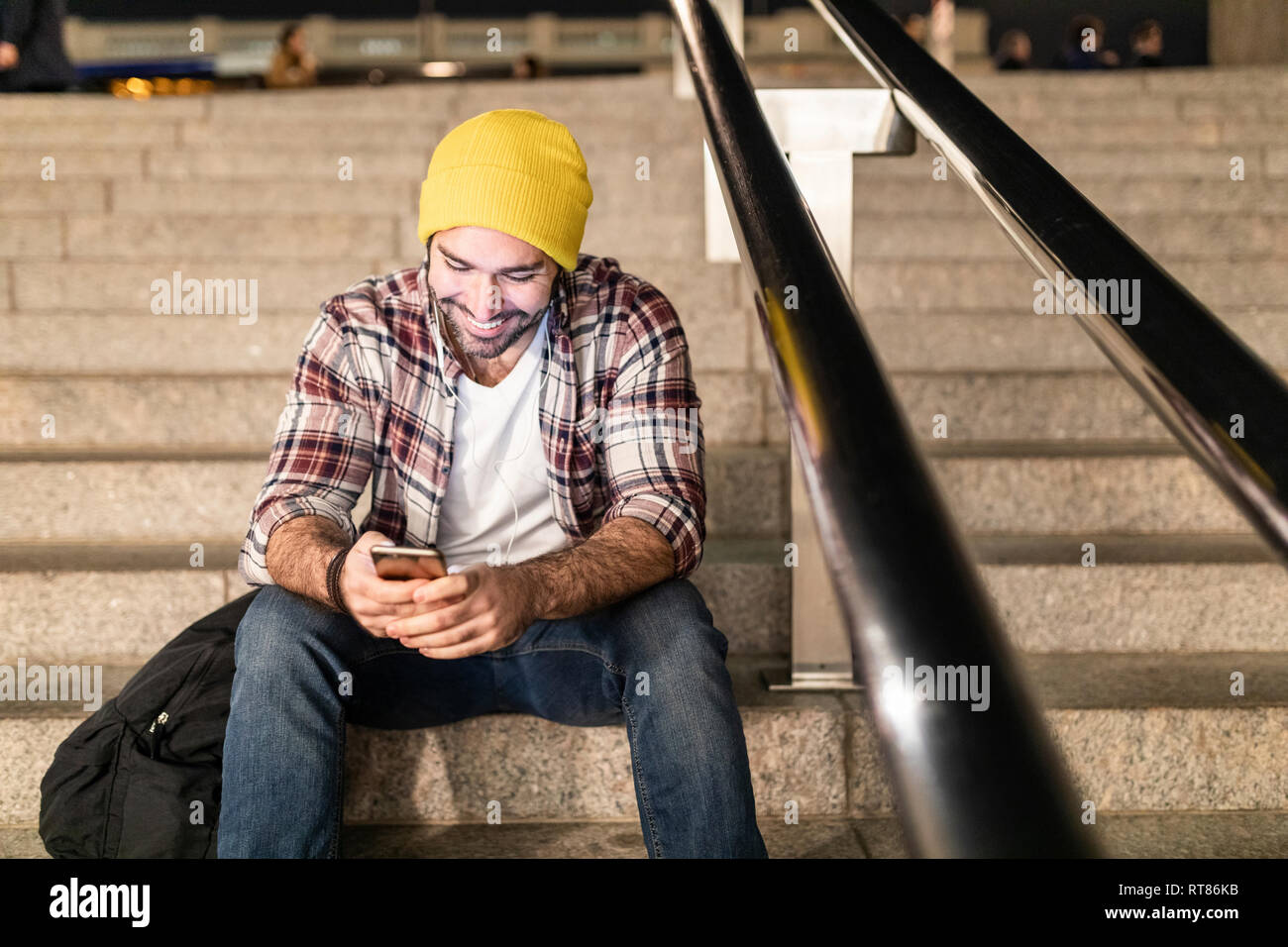 UK, London, man sitting on a staircase and looking at his phone on a night commute - Stock Image
