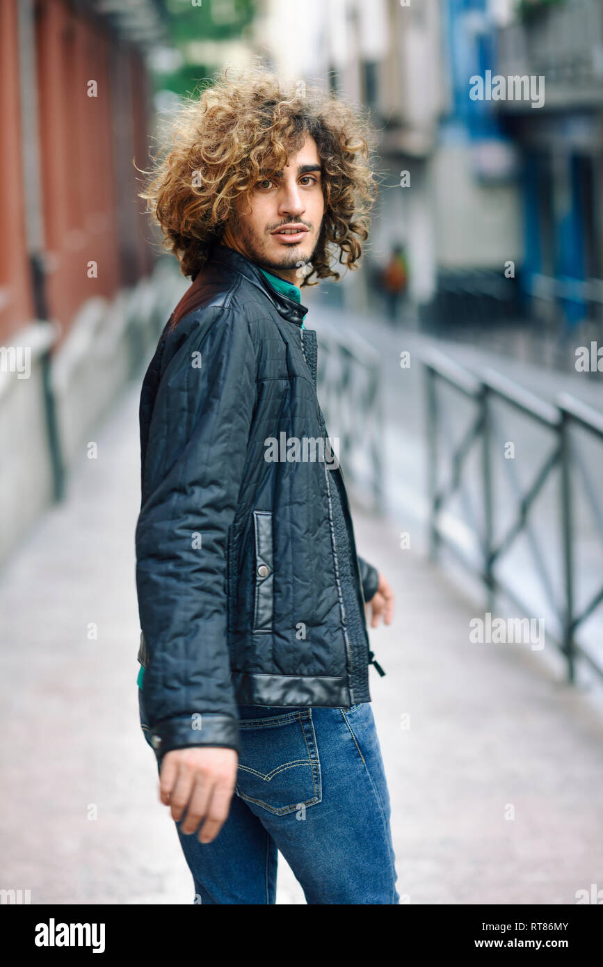 Spain Granada Portrait Of Young Man With Curly Hair Walking On Pavement Stock Photo Alamy