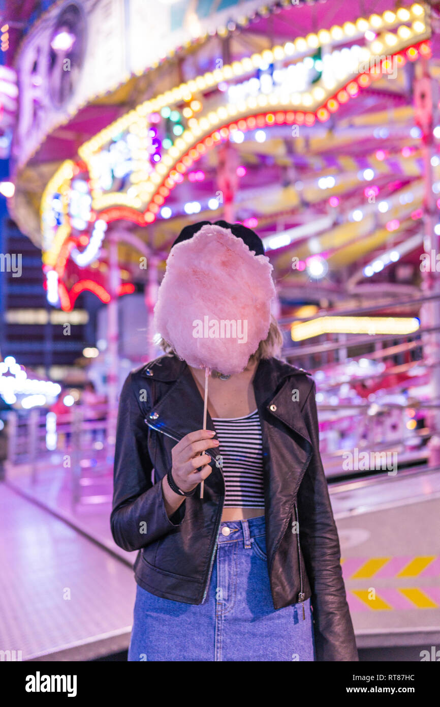Teenage girl hiding her face behind pink candyfloss at fair - Stock Image
