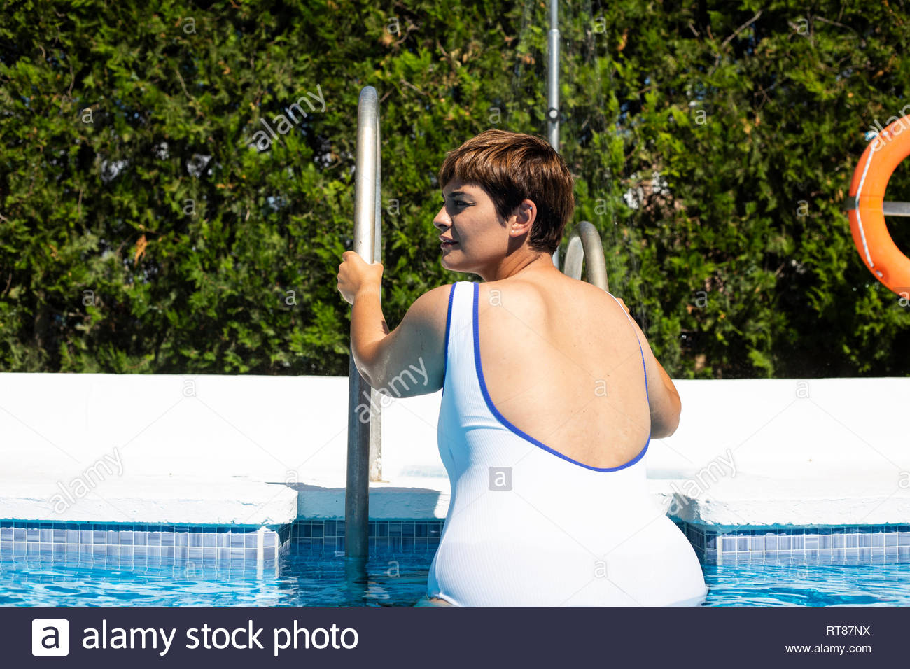 Back view of plump young woman leaving swimming pool - Stock Image