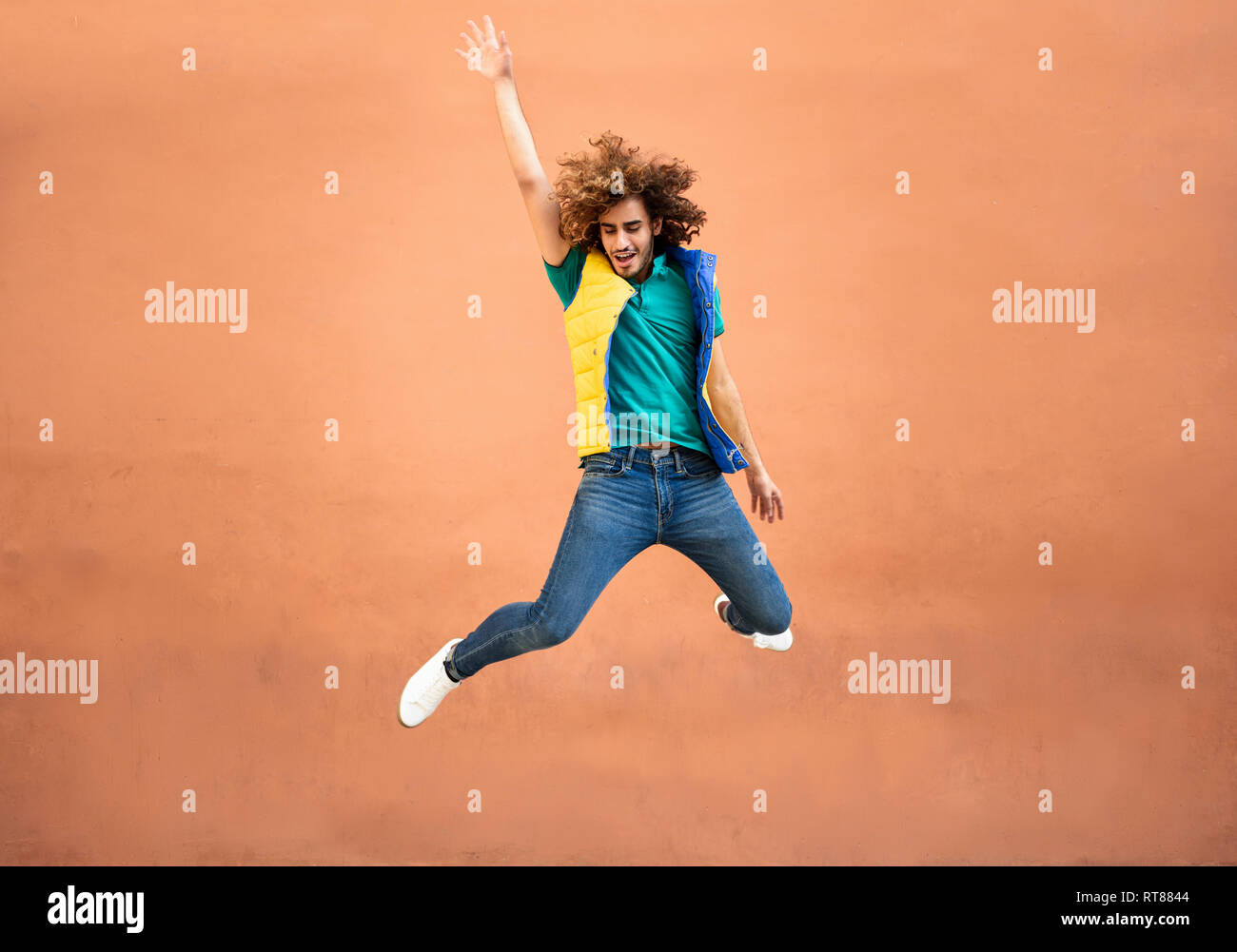 Happy young man with curly hair wearing waistcoat jumping in the air - Stock Image