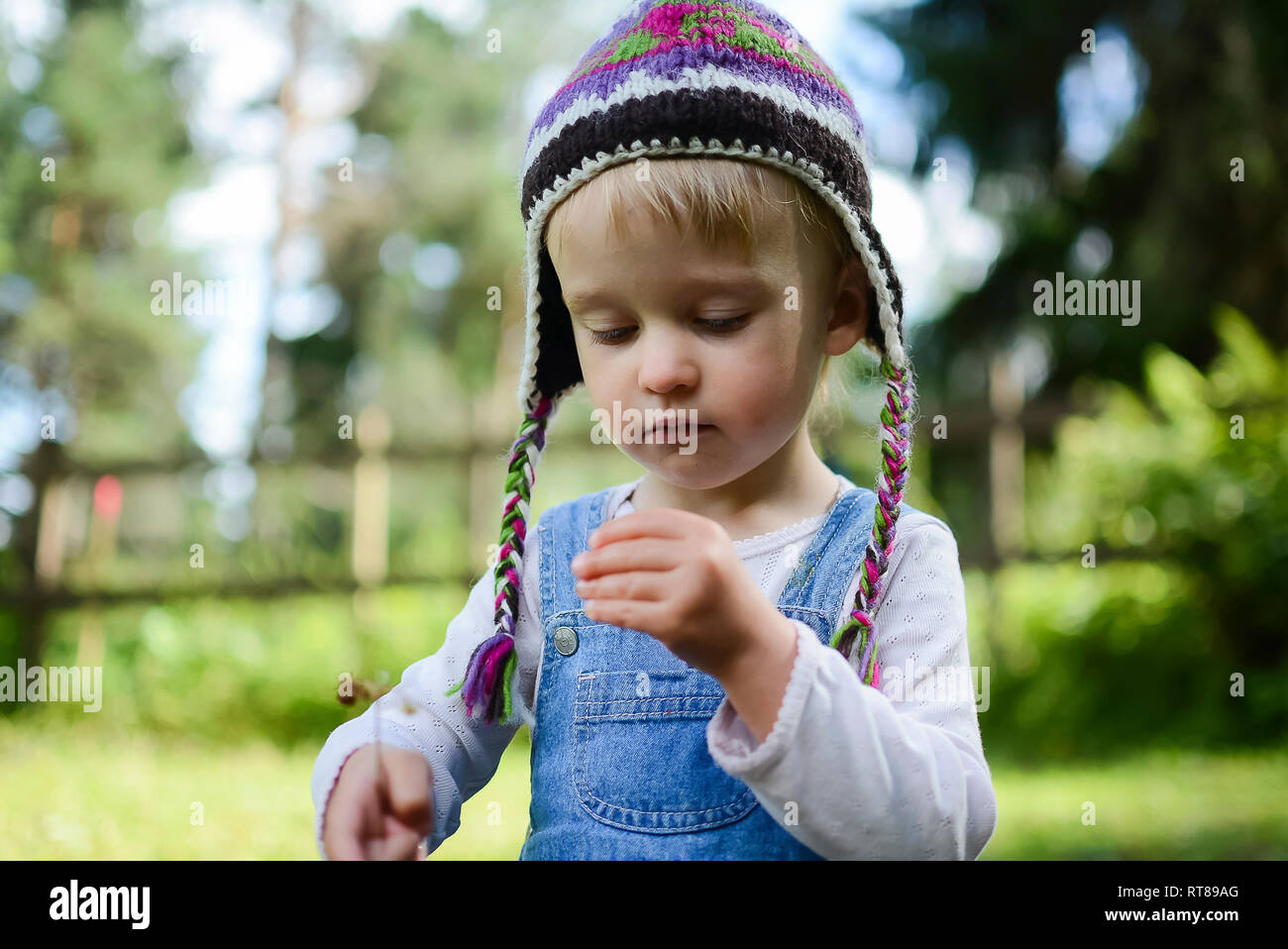 Portrait of little girl wearing knitted hat watching something in her hand - Stock Image