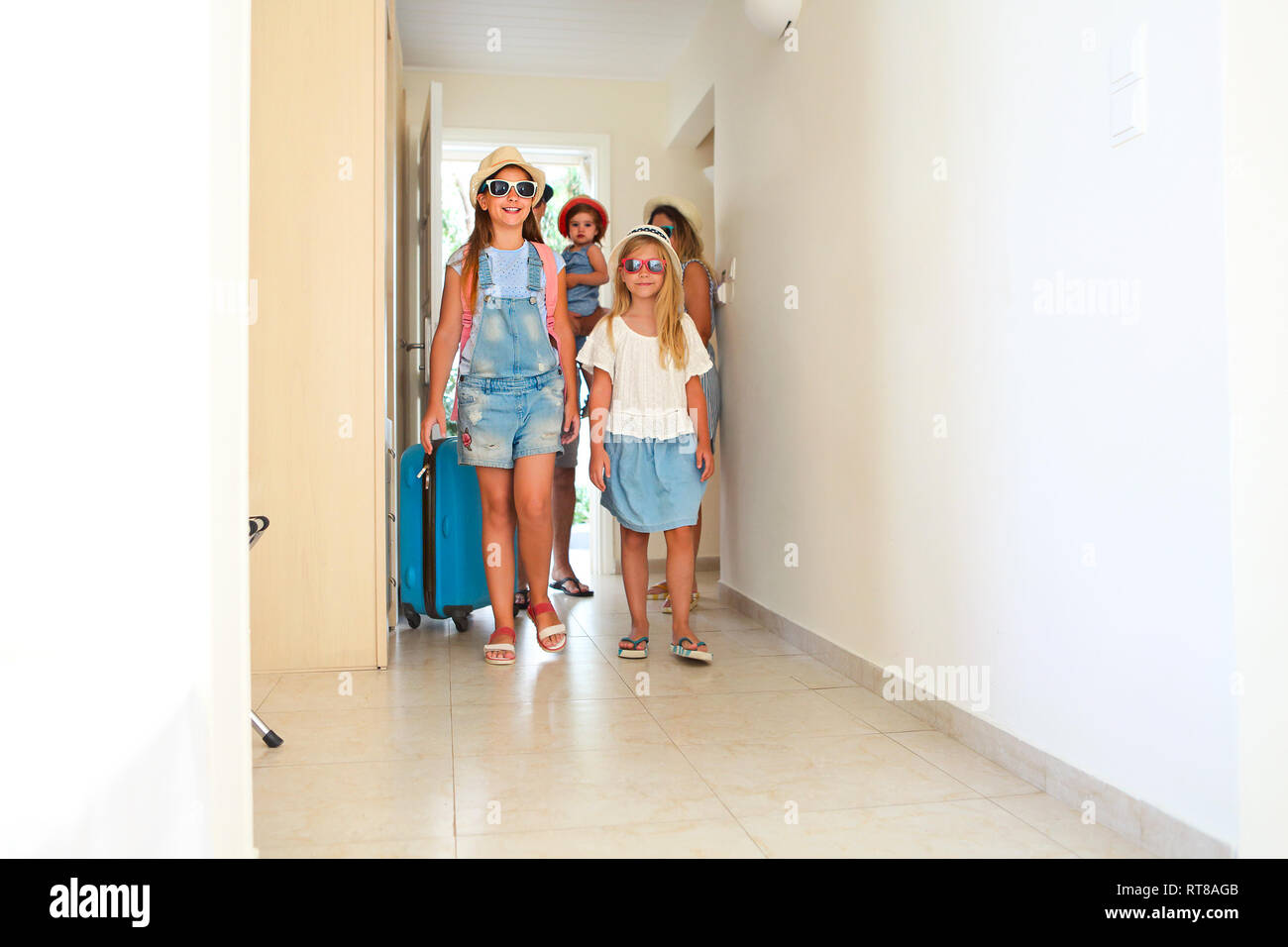 Young family with three kids with luggage in hotel room - Stock Image