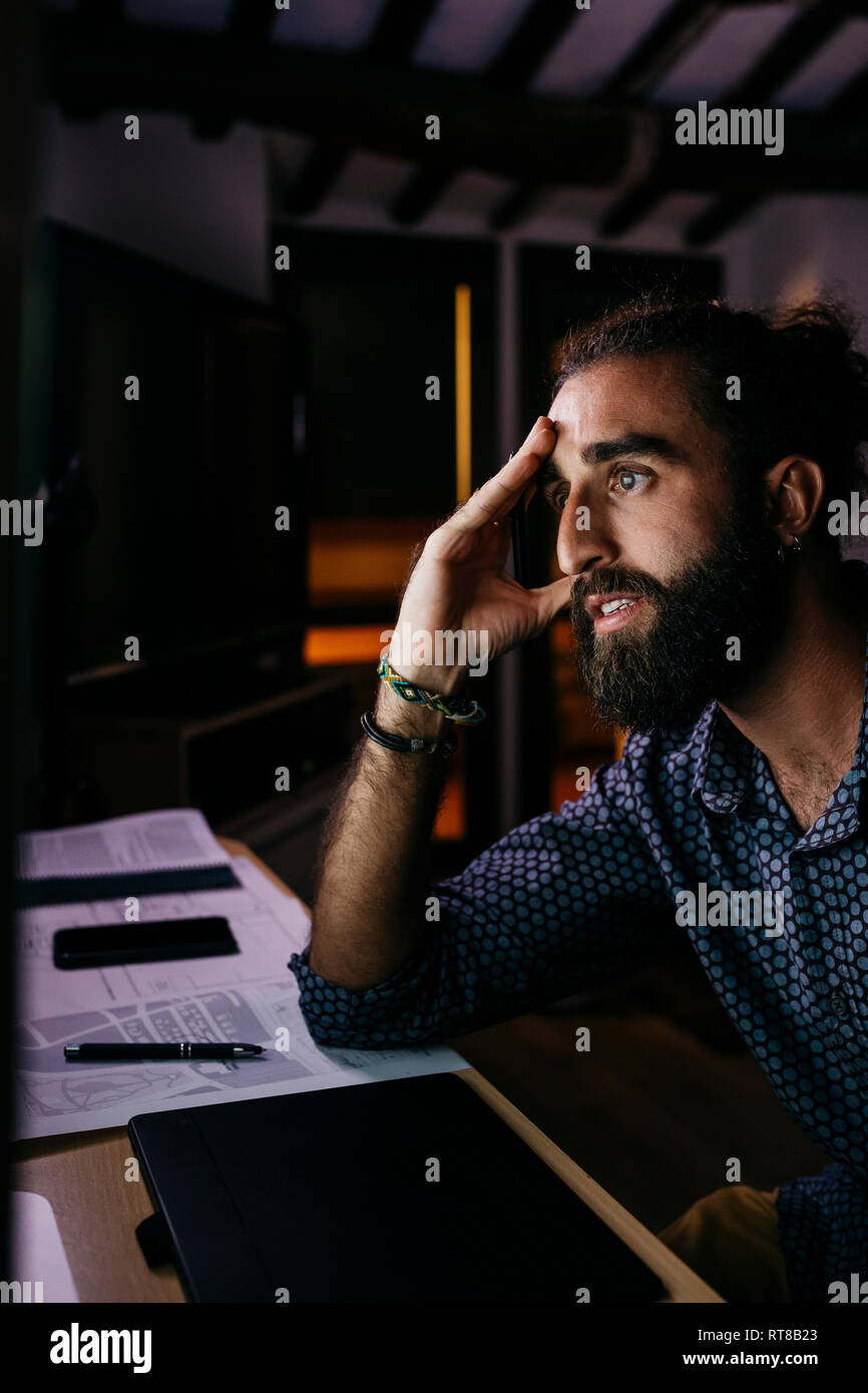 Young man working hard on a new project at home at night - Stock Image