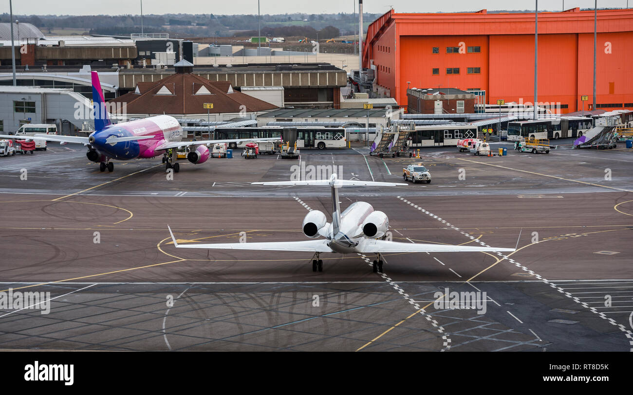 Business jet arriving on the apron area of Luton airport, England. - Stock Image