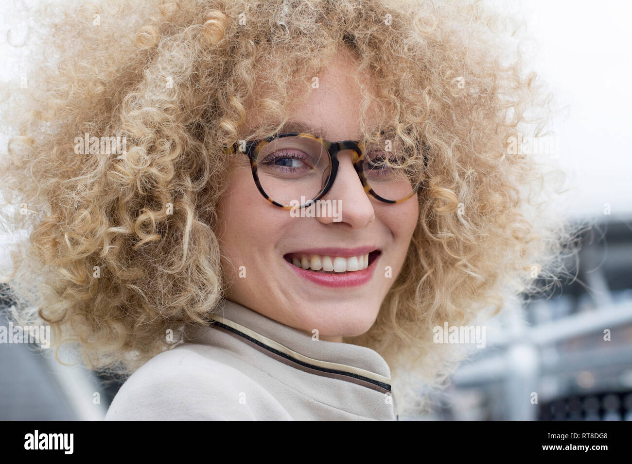 Portrait of smiling blond woman with ringlets wearing fashionable glasses Stock Photo