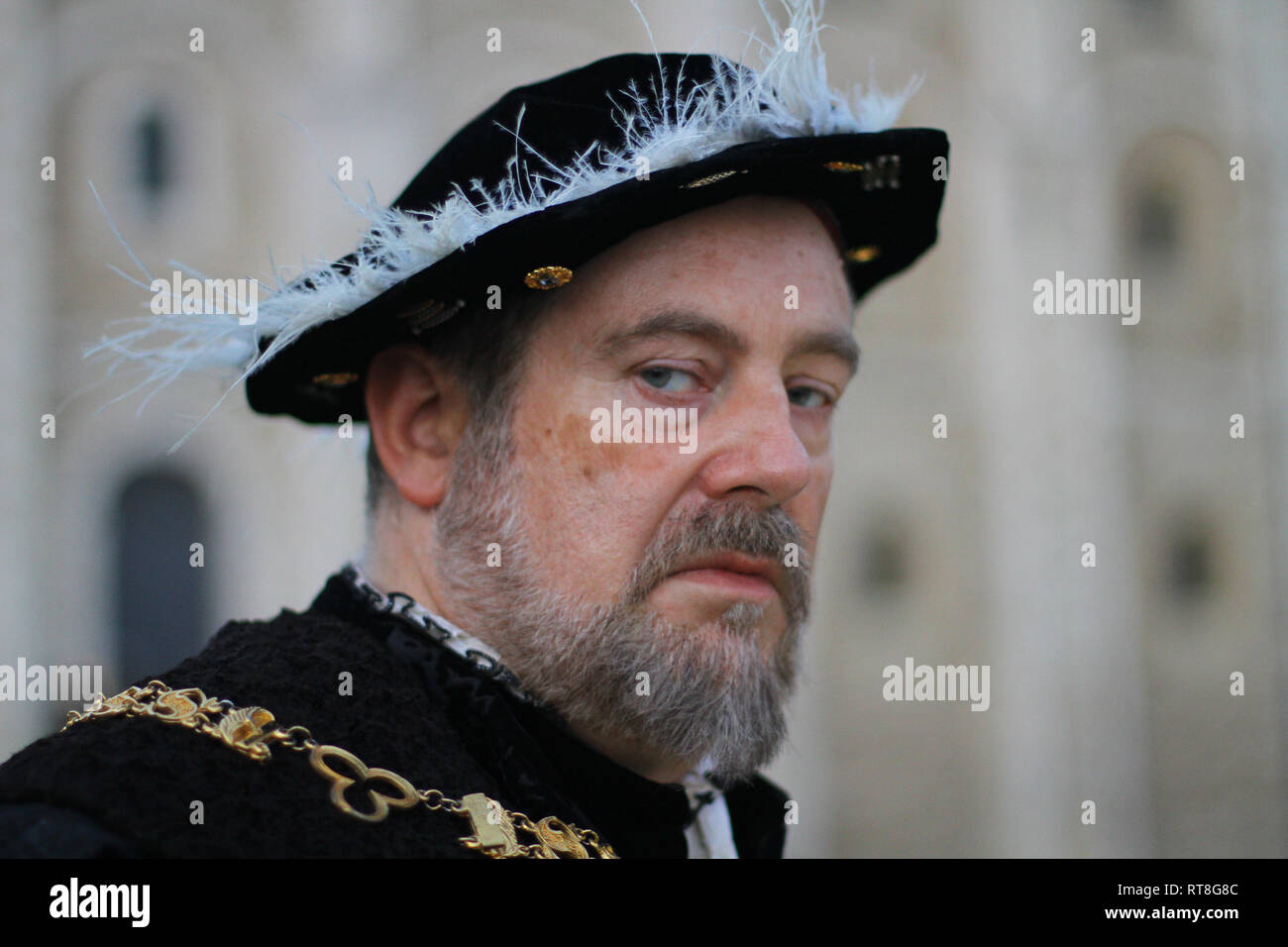 Portrait of a modern day Henry VIII wearing authentic Tudor dress taken at The Tower of London- he is old and has a greying beard and looks scary - Stock Image