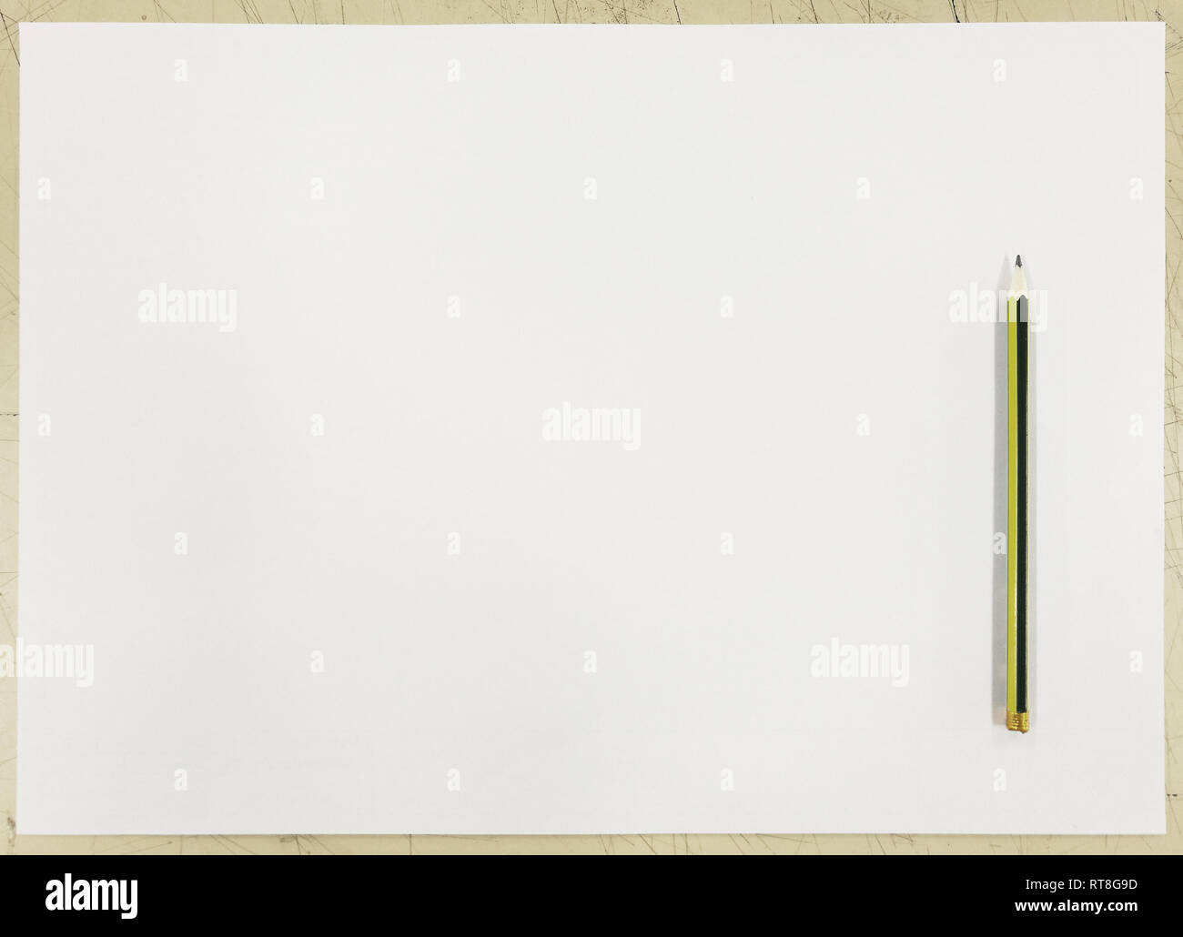 white paper on table and a single pencil on top. Top view background for idea formulation and writing concepts. - Stock Image