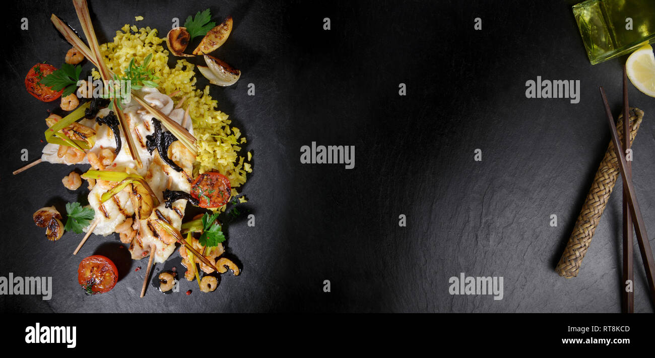 Flatfish Fillet with Shrimps on black Slate - Stock Image