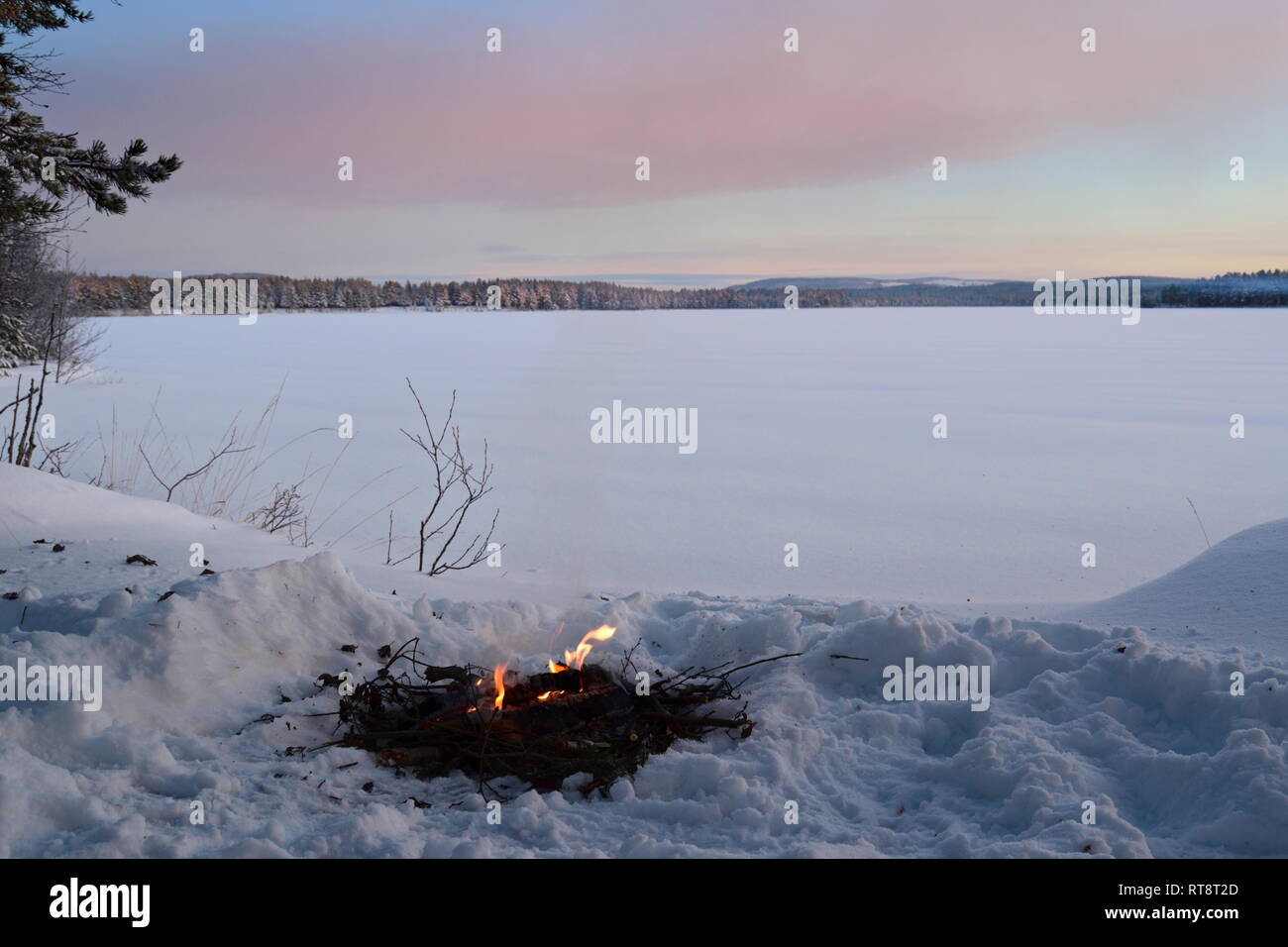 A fire is burning in the snow at the shore of an ice-covered lake as the sun is setting on a cold winter day. Stock Photo