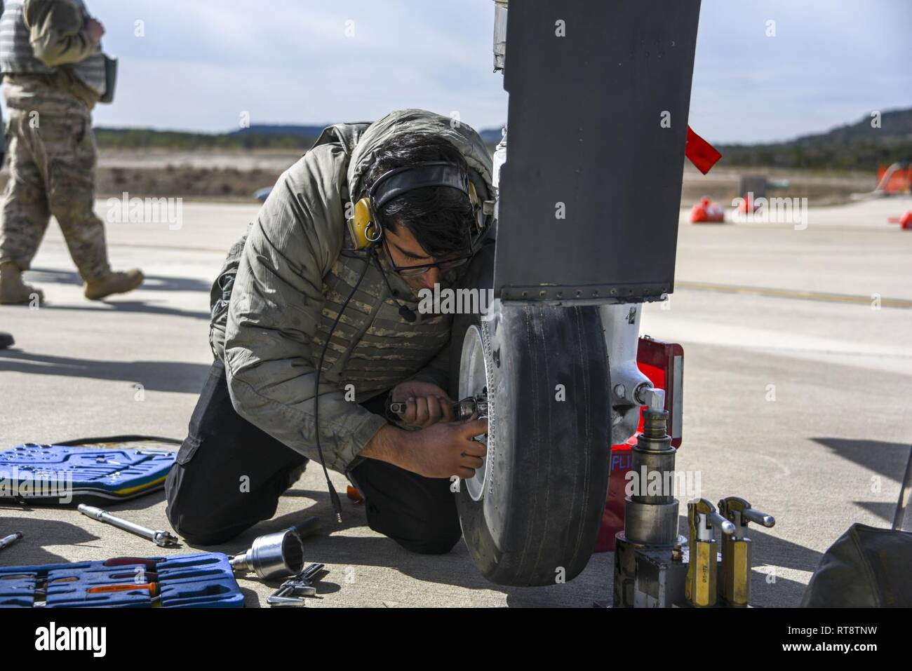 U.S. Air Force Staff Sgt. Anmoledeep Sandhu, 354th Fighter Squadron crew chief, changes the tire on an A-10 Thunderbolt II during operation Pegasus Forge Jan. 28, 2019. During Operation Pegasus Forge, the 355th Wing's dynamic forward adaptive basing team's mission was to wield rapid combat power from a position of advantage with minimal footprint. - Stock Image