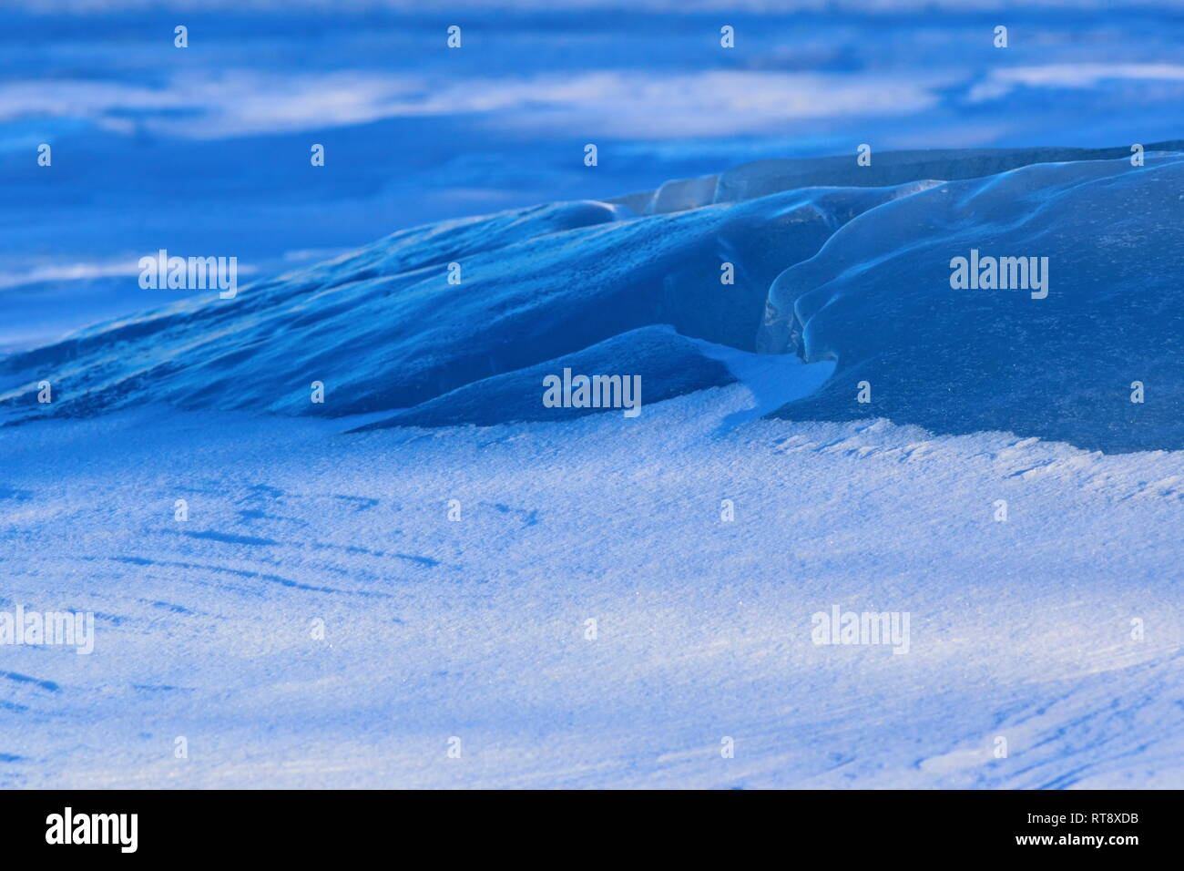 The wind has formed patterns in the snow covering a frozen lake. Stock Photo