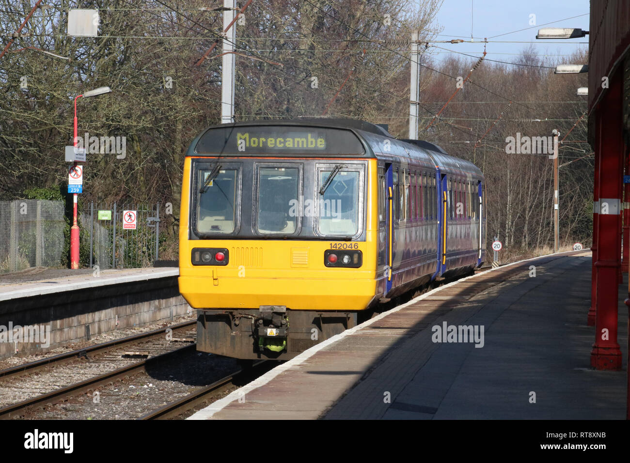 Class 142 Pacer diesel multiple unit, number 142 046, in Northern livery leaving at Lancaster railway station, platform 2, on 25th February 2019. - Stock Image