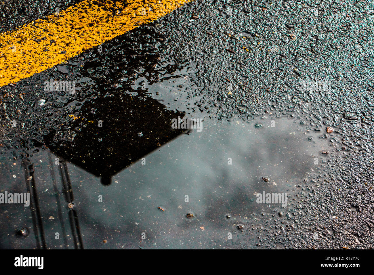 A wet road with a yellow line and reflection - Stock Image