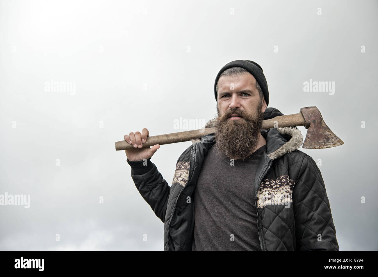 Handsome man hipster or guy with beard and moustache on serious face in hat and jacket holds rusty axe with wooden hilt outdoor against cloudy sky on natural background, copy space - Stock Image