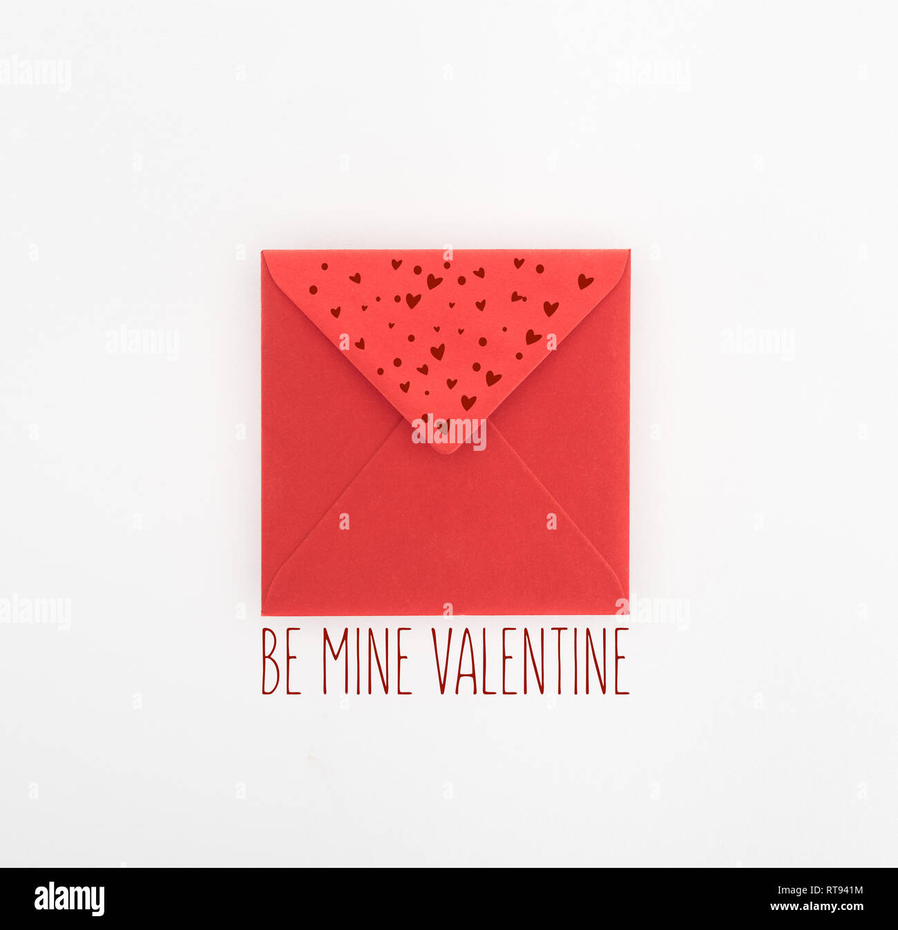 flat lay with red envelope isolated on white, st valentine day concept with 'be mine valentine' lettering - Stock Image