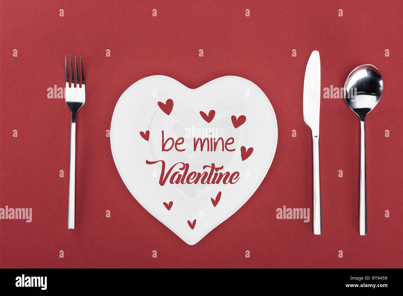 view from above of heart shaped plate with 'be mine valentine' lettering and cutlery isolated on red, st valentine day concept - Stock Image