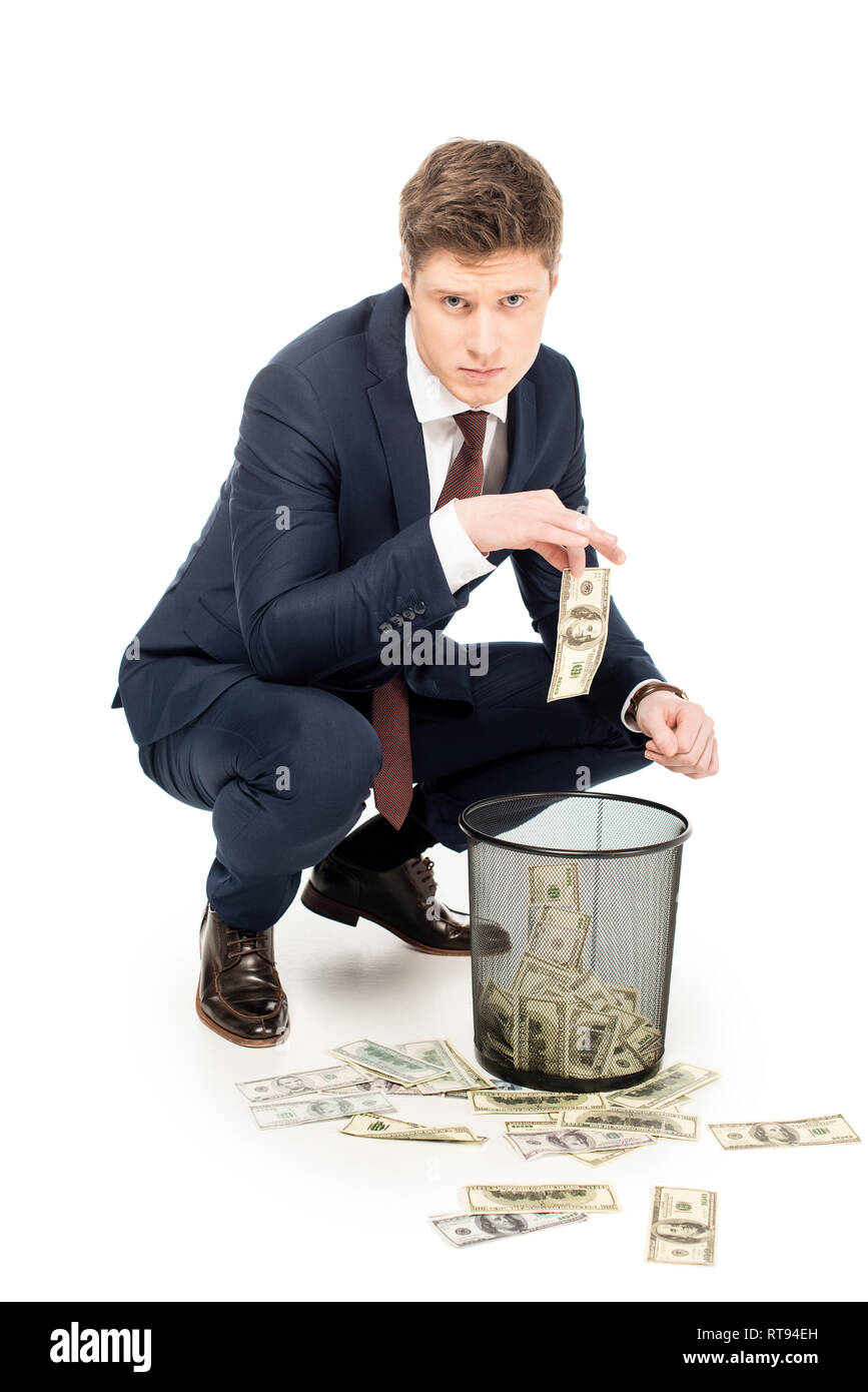 confused businessman taking dollar banknotes from trash can on white - Stock Image