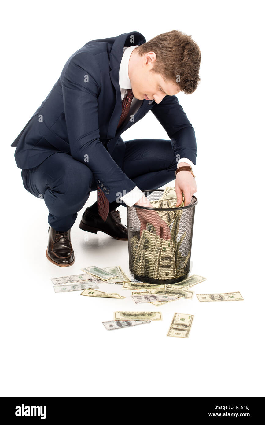 young businessman taking money from trash can on white - Stock Image