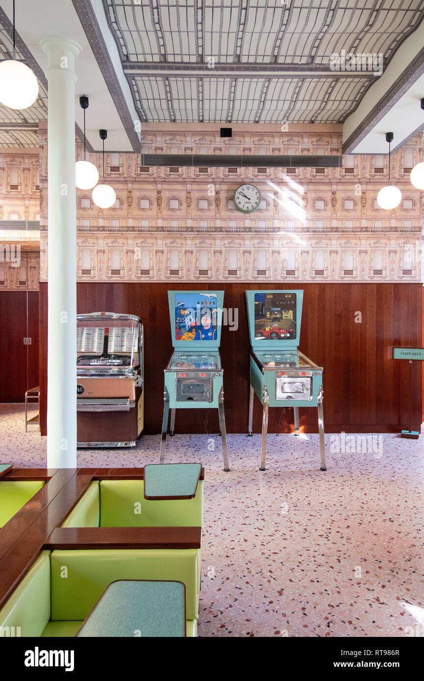 Pinball machines, juke box and pastel furniture at Bar Luce, Wes Anderson-inspired bar and cafe in the Fondazione Prada district of Milan, Italy - Stock Image